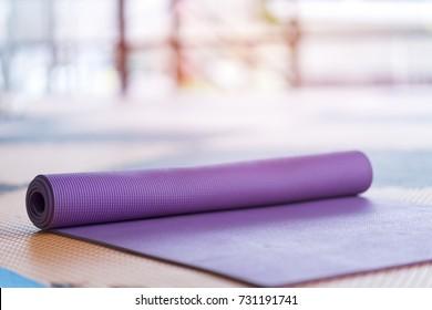 Purple yoga mat on floor in Yoga studio.