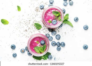 Purple yogurt or smoothie with blueberries, chia seeds and mint leaves in glass jars on white background, flat lay, top view
