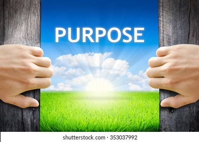 """Purpose. Hand opening an old wooden door and found wording """"Purpose"""" over green field and bright blue Sky Sunrise."""