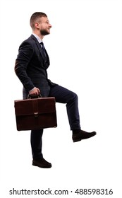 Purposeful businessman comes up with a briefcase in his hands
