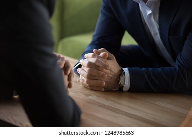 Purposeful confident restrained businessmen in suits sit at table opposite each other, close up male clenched hands in lock at desk. Complexity of decision self-control in stressful situation concept - Shutterstock ID 1248985663