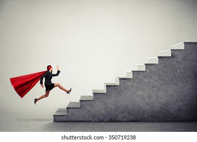 purposeful superwoman in red cloak running up stairs over light grey background
