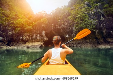 Purposeful woman paddling the kayak in the calm bay Halong among picturesque karst mountains at sunset.Vietnam. Mountains and sea landscape, travel to Asia, happiness emotion, summer holiday concept.