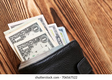 a purse with the American dollars is isolated on a wooden background