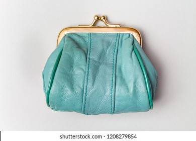 Purse for coins.Wallet for change. Leather purse. Turquoise purse on a grey background. Color of the trend.The concept of poverty