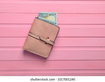 A purse with dollar bills on a pink wooden table. Top view.