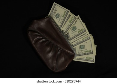Purse with dollars on a black background