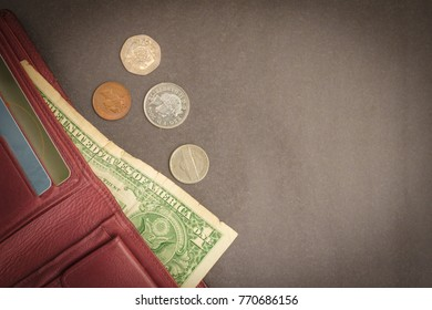 A purse with small money. The hour of reckoning, financial obligations, alimony. Gray background, muted tone. View from above. Vignetting.