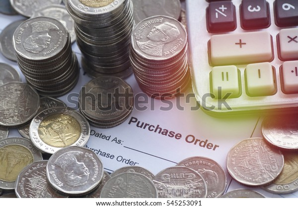 purshase order paper with coin and calculator on wood table