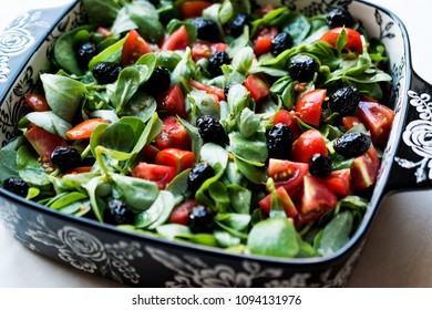 Purslane Salad with Tomatoes and Black Olives in Porcelain Bowl.