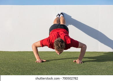 Push up fitness man training using wall doing decline pushup at outdoor gym. Male fitness athlete doing advanced push-ups on grass park.