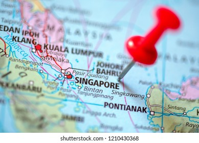 Push pin on the territory of Singapore on the world map