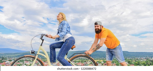 Push and promoting. Impulse to move. Man pushes girl ride bike. Support helps believe in yourself. Feel impulse to start moving. Woman rides bicycle sky background. Girl cycling while man support her.