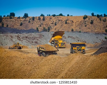 Push Pull Tip. Three yellow mining trucks move overburden in an open cut coal mine, Fossil fuel industry, Environmental challenge. All logos removed.