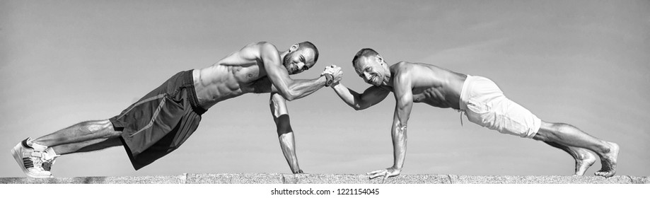 Push ups challenge. Men motivated workout together. Sportsmen improves his strength by push up exercise. Improve endurance by push ups. Men doing push up outdoor blue sky background. Teamwork concept.