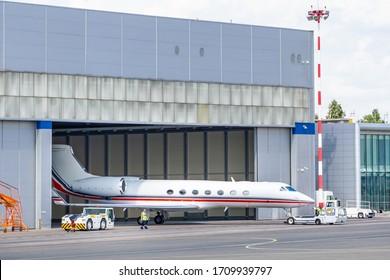 Der Rückwärtswagen, der den Geschäftsflugzeug vom Hangar zum Taxistreifen besteuert