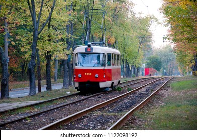 Pushcha Voditsa, Ukraine - October 02, 2016: public transportation of tram red color on rail track outdoor in green autumn deep forest on natural background
