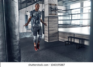 Pushing hard to win. Full length of young African man in sport clothing skipping rope while exercising in the gym