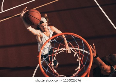 Pushing hard to win. Top view of young man in sports clothing scoring a slam dunk while playing basketball with friends outdoors