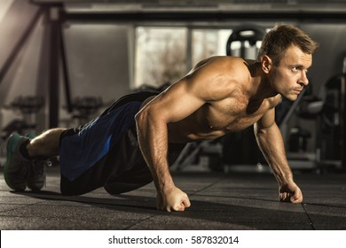 Pushing his limits. Full length shot of a shirtless man with toned muscular athletic body doing pushups working out at the gym confidence agility strength competition sports training concept