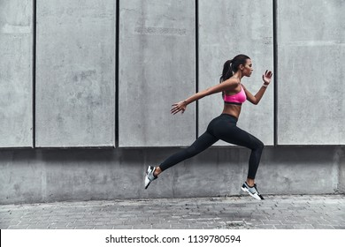 Pushing to the limit. Modern young woman in sports clothing jumping while exercising outdoors