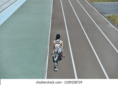 Pushing to the limit. Top rear view of young woman in sports clothing standing on the start line while running outdoors