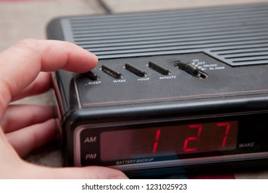 Pushing the sleep or snooze button on an old analog alarm clock