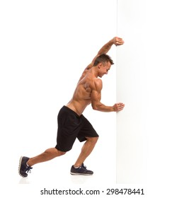 Pushing The Wall. Muscular man in sport shorts and sneakers pushing a white wall.  Full length studio shot isolated on white.