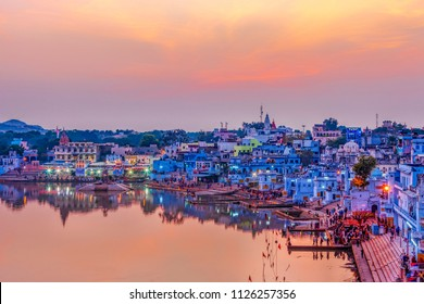 Pushkar Holy Lake at sunset. Hindu pilgrims bathing in sacred Lake Pushkar (Sarovar) on ghats. Countless people in colourful attire gather to take a dip in the Holy Lake and pray to deities.