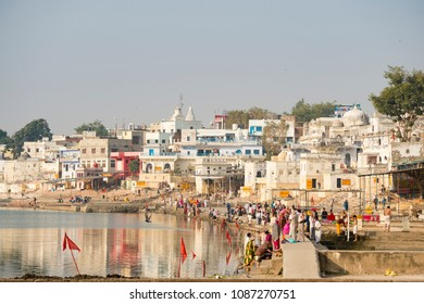 PUSHKAR, INDIA - 07 DECEMBER 2017. Hindu devotees pilgrims bathing in sacred Pushkar lake (Sagar) on ghats of Pushkar, Rajasthan. Pushkar is holy city for Hinduists and famous for many Hindu temples