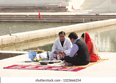 PUSHKAR, INDIA - December 2017: Hindu Brahman performs puja or ritual on the shore of holy lake Pushkar. Local people worship Brahma, Hindu God in Pushkar, Rajasthan, India