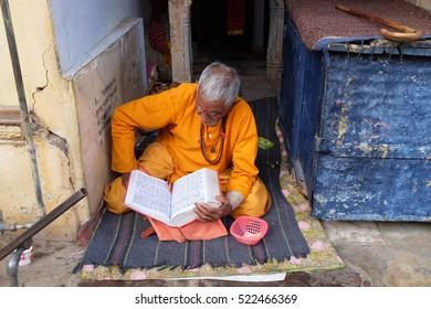 PUSHKAR, INDIA - FEBRUARY 17: A Priest sitting on the entrance of Ghat in Pushkar, India on February 17, 2016.