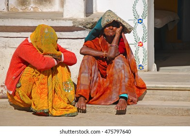 PUSHKAR, INDIA - JAN 5, 2015: Two elderly Indian woman in sari's with covered heads sit in doorway of home.