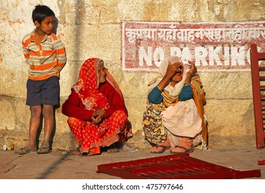 PUSHKAR, INDIA - JAN 5, 2015: Boy and Two elderly Indian woman in sari's with covered heads sit in doorway of home.