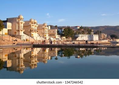 PUSHKAR, INDIA - JANUARY 5, 2019: Pilgrims walking on Varaha Ghat along Pushkar Sarovar lake. It is located in Ajmer district of the Rajasthan state. Pushkar Lake is a sacred lake of the Hindus.