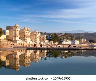 PUSHKAR, INDIA - JANUARY 5, 2019: Pilgrims walking on Ghat along Pushkar Sarovar lake. It is located in Ajmer district of the Rajasthan state. Pushkar Lake is a sacred lake of the Hindus.