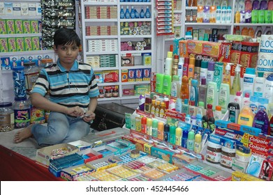 PUSHKAR, INDIA - MARCH 14, 2006: A child sitting next to the merchandise in the family store