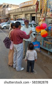 PUSHKAR, INDIA - NOV 19, 2015: Unknown group of people in the streets. A family buys an balloon for the child at a street trader.