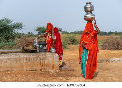 PUSHKAR, INDIA - NOVEMBER 04, 2019: Kalbeliya gypsy women in colorful clothes collect and carry on their head drinking water at public tap in desert on November 04, 2019 in Pushkar, Rajasthan, India.