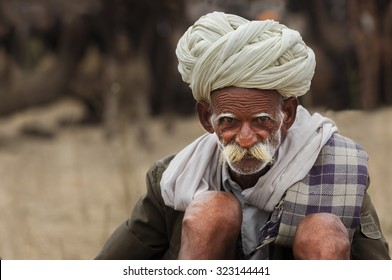 Pushkar, India - November 1, 2014 : Unidentified old Indian tribal man with his traditional dress and turban, sits on the sands of deseret in Pushkar Camel Fair,India
