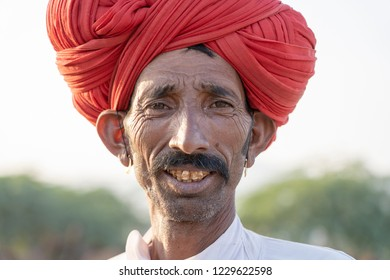 PUSHKAR, INDIA - NOVEMBER 12, 2018 : Indian man in the desert Thar during Pushkar Camel Mela near holy city Pushkar, Rajasthan, India. This fair is the largest camel trading fair in the world.