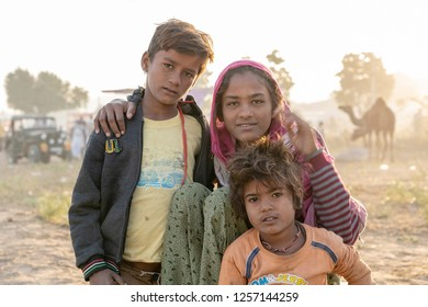 PUSHKAR, INDIA - NOVEMBER 12, 2018 : Indian boy and girl in the desert Thar on time Pushkar Camel Mela near holy city Pushkar, Rajasthan, India