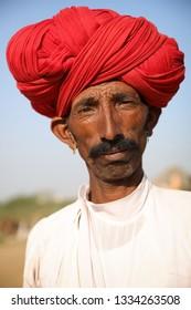 PUSHKAR, INDIA - NOVEMBER 12, 2018: Unidentified Rabari tribal man from Gujarat at the Pushkar Camel Fair, Rajasthan. The fair is the largest camel fair in India.