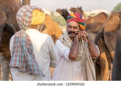 PUSHKAR, INDIA - NOVEMBER 13, 2018 : Indian man in the desert Thar during Pushkar Camel Mela near holy city Pushkar, Rajasthan, India. This fair is the largest camel trading fair in the world.