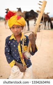 PUSHKAR, INDIA - NOVEMBER 13, 2018: Unidentified young Gypsy musician at the Pushkar Camel Fair, Rajasthan. The fair is the largest camel fair in India.