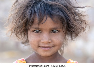 PUSHKAR, INDIA - NOVEMBER 13, 2018 : Indian young girl in the desert Thar on time Pushkar Camel Mela near holy city Pushkar, Rajasthan, India, close up portrait