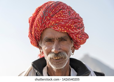 PUSHKAR, INDIA - NOVEMBER 13, 2018 : Indian man in the desert Thar during Pushkar Camel Mela near holy city Pushkar, Rajasthan, India. This fair is the largest camel trading fair in the world.