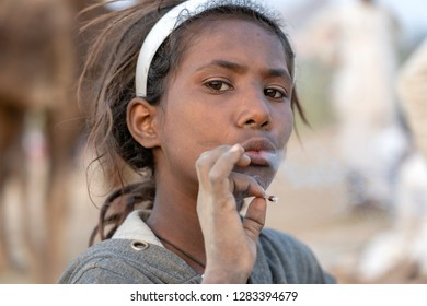 PUSHKAR, INDIA - NOVEMBER 14, 2018 : Indian young girl smoking cigarette in the desert Thar on time Pushkar Camel Mela near holy city Pushkar, Rajasthan, India, close up portrait