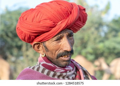 PUSHKAR, INDIA - NOVEMBER 14, 2018 : Indian man in the desert Thar during Pushkar Camel Mela near holy city Pushkar, Rajasthan, India. This fair is the largest camel trading fair in the world.