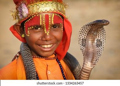 PUSHKAR, INDIA - NOVEMBER 14, 2018: Unidentified Gypsy snake charmer at the Pushkar Camel Fair, Rajasthan. The fair is the largest camel fair in India.